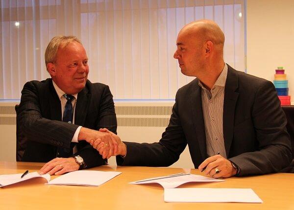 Cees Meijer (SRA) en Chris Textor (TCC) tekenen het NetDimensions contract